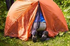 Mann ` s Beine in den schmutzigen touristischen Stiefeln halten heraus an in das Zelt fest Stockfotografie