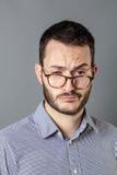 Mann 30s, der schläfrig, gleichgültig und mit Brillen unten unvorsichtig schaut lizenzfreies stockbild