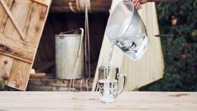 Mann ` s Hände gießen Wasser vom Eimer von gut in den Wasserfilter, der draußen auf dem Holztisch steht stock video footage