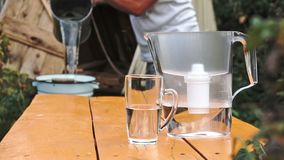 Mann ` s Hände gießen Wasser vom Eimer von gut in den Wasserfilter, der draußen auf dem Holztisch steht stock video