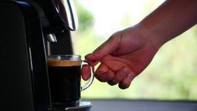 Mann ` s Hand nimmt einen Becher mit einer FOCA Kaffeeströme von der Kaffeemaschine zu Hause Gesamtlänge auf Lager stock footage