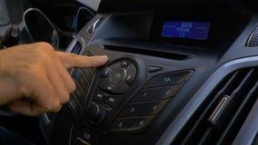 Mann ` s Hand setzt die Scheibe in den Autospieler Knöpfen Sie Steuerung für Digitalschallplattespieler in einem Auto Hand setzt  Stockfotos