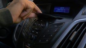 Mann ` s Hand setzt die Scheibe in den Autospieler Knöpfen Sie Steuerung für Digitalschallplattespieler in einem Auto Hand setzt  Lizenzfreies Stockfoto