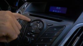 Mann ` s Hand setzt die Scheibe in den Autospieler Knöpfen Sie Steuerung für Digitalschallplattespieler in einem Auto Hand setzt  Stockfoto