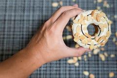 Mann ` s Handgriff ein weißer Schokolade Donut Stockfotografie