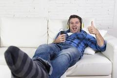 Mann 20s oder 30s, der den Spaß hört Musik mit Handy und Kopfhörern hat Lizenzfreie Stockfotografie
