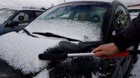 Mann s?ubert das Auto vom Schnee