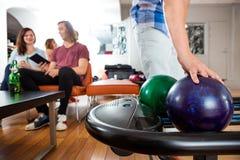 Mann-Sammeln-Bowlingkugel vom Gestell Stockbilder