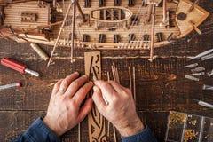Mann sammelt das Fahrzeugmodell auf dem Holztisch Stockfotografie