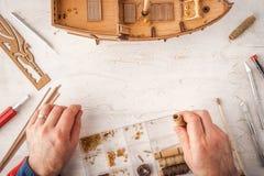 Mann sammelt Schiffsmodell auf einer weißen Tabelle Lizenzfreie Stockfotos