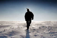 Mann Sankt im Hut gehend auf Schnee-Feld Lizenzfreie Stockfotografie