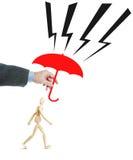 Mann schützt eine andere Person vor Härten, indem er ihn mit einem Regenschirm bedeckt Lizenzfreie Stockfotografie