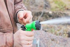 Mann schaltet den Schlauch für Bewässerungsanlagen mit a ein Lizenzfreie Stockbilder