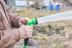 Mann schaltet den Schlauch für Bewässerungsanlagen mit einem Sprüher ein Lizenzfreie Stockfotografie