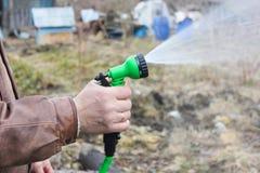 Mann schaltet den Schlauch für Bewässerungsanlagen mit einem Sprüher ein schließen Sie ein Stockfoto
