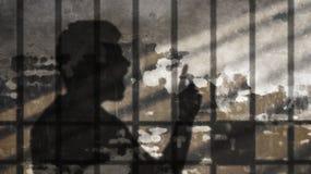 Mann-Schatten, der unter Gefängnis-Stangen spricht Lizenzfreie Stockfotografie