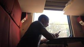 Mann Schattenbild, dasreise im Zug Wagenholding sitzt, sitzt am Fenster eine Smartphone Eisenbahn in den Kopfhörern stock video