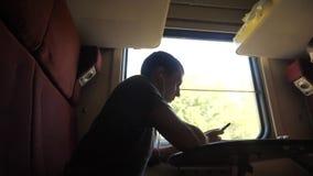 Mann Schattenbild, dasreise im Zug Wagenholding sitzt, sitzt am Fenster eine Smartphoneeisenbahn und -c$trinken stock footage