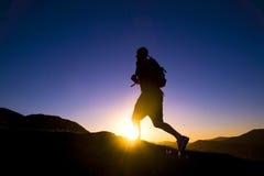 Mann-Schattenbild-laufendes Sonnenuntergang-Gebirgszug-Konzept stockfoto