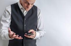 Mann schaut frustriert, gereizt und hält sein intelligentes Telefon stockbilder