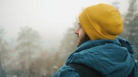 Mann schaut um stehend auf die Oberseite des Felsens in den Bergen, die mit Nebel bedeckt werden stock footage
