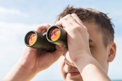 Mann schaut zum binokularen Stockbilder