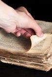 Mann schlägt durch eine alte Kopie der Bibel leicht Lizenzfreie Stockfotografie