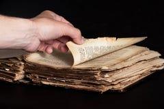 Mann schlägt durch eine alte Kopie der Bibel leicht Stockfotos