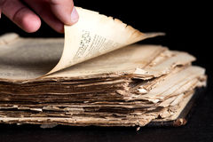 Mann schlägt durch eine alte Kopie der Bibel leicht Stockfoto