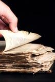 Mann schlägt durch eine alte Kopie der Bibel leicht Stockfotografie