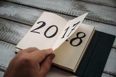 Mann schlägt Notizblockblatt auf Tabelle leicht 2017 dreht sich, 2018 sich öffnet Lizenzfreies Stockfoto