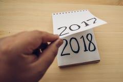Mann schlägt Notizblockblatt auf Tabelle leicht 2017 dreht sich, 2018 sich öffnet Stockfotografie