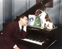 Mann schlafend am Klavier mit Hund (alle dargestellten Personen sind nicht längeres lebendes und kein Zustand existiert Lieferant stockbild