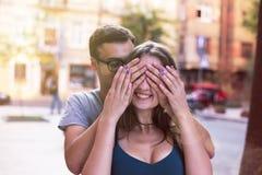 Mann schließt seine Augen für das Mädchen, das ihr Überraschungslächeln macht Stockfoto