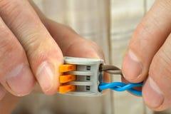 Mann schließt die verdrehten Enden der Drähte unter Verwendung des kompakten verstärkenden Verbindungsstücks an stockfoto