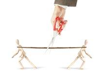 Mann schneidet ein Seil, dem zwei Männer herein verschiedene Richtungen ziehen Stockfoto