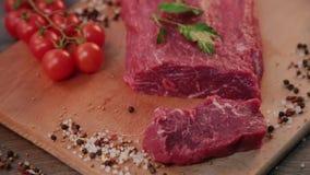 Mann schneidet rohes Rindfleisch auf hölzernem Brett stock video