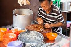 Mann schneidet Schweinefleisch für Reisbrei lizenzfreies stockfoto