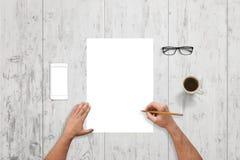 Mann schreiben auf leeres Papier auf weißem hölzernem Schreibtisch Weißes intelligentes Telefon mit lokalisiertem Schirm für Mode Stockbild