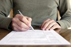 Mann-Schreiben auf Papier mit Feder auf Tabelle Stockbilder