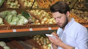 Mann schreiben in sein Notizbuch am Supermarkt stock footage