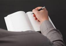 Mann-Schreibens-Anmerkung über sein Notizbuch Lizenzfreie Stockfotografie