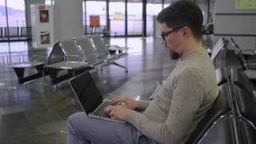 Mann schreibt auf Tastatur des Laptops in der Halle im Flughafen stock footage