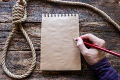 Mann schreibt eine Selbstmordanmerkung stockbilder