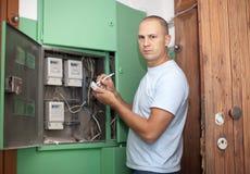 Mann schreibt Messinstrumentmesswerte des Stroms neu lizenzfreie stockfotos