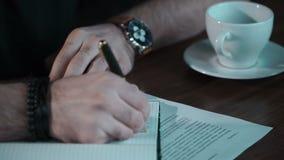 Mann schreibt in Schreibheft stock footage