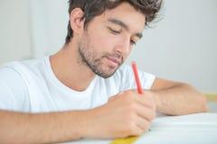 Mann am Schreibtisch mit Machthaber und Bleistift Lizenzfreie Stockbilder