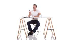 Mann am Schreibtisch und am Telefon lizenzfreie stockbilder