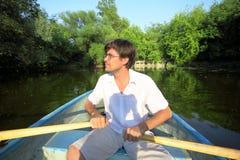 Mann schwimmt hinunter den Fluss auf einem Boot Stockfotos