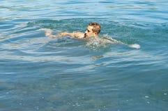 Mann schwimmt im Teich lizenzfreie stockfotos